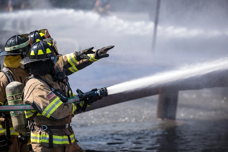 Firefighters from the Valdosta Fire Department (VFD) signal to firefighters from the 23d Civil Engineer Squadron during live-fire training, April 25, 2018, at Moody Air Force Base, Ga.  Firefighters from the 23d Civil Engineer Squadron and VFD participated in the training to gain more experience fighting aircraft fires and to work together as a cohesive team while still practicing proper and safe firefighting techniques. (U.S. Air Force photo by Airman Eugene Oliver)