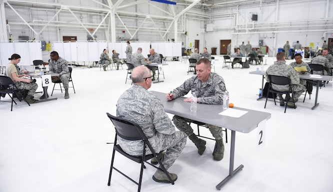 U.S. Air Force Senior Master Sgt. Matthew Woods, 133rd Medical Group, talks to Col. Charlie Thigpen, left, deputy director for the Office of the Air Surgeon, about what is covered at the health history station in St. Paul, Minn., April 20, 2018.
