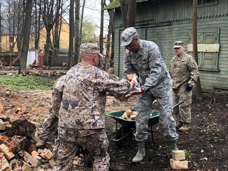 "Soldiers and airmen from the Michigan National Guard participate in a volunteer work project at the National Social Care Center, Riga affiliate, as part of Latvia's ""National Clean-up Day,"" along with four soldiers from the 407th Civil Affairs Team stationed at Lielvārde Air Base, two personnel from the U.S. Embassy Office of Defense Cooperation, and members of Latvia's National Guard (Zemessardze) (Michigan National Guard photo by 1st Lt. Andrew Layton/released)."