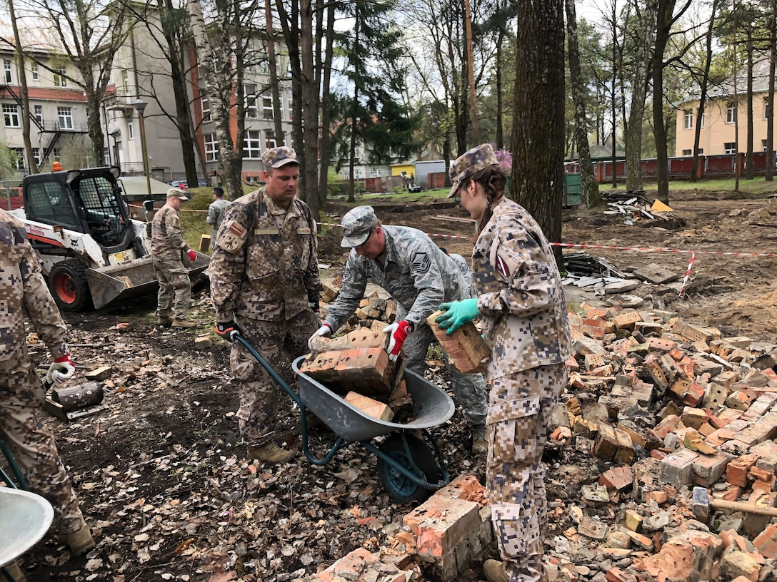 """Soldiers and airmen from the Michigan National Guard participate in a volunteer work project at the National Social Care Center, Riga affiliate, as part of Latvia's """"National Clean-up Day,"""" along with four soldiers from the 407th Civil Affairs Team stationed at Lielvārde Air Base, two personnel from the U.S. Embassy Office of Defense Cooperation, and members of Latvia's National Guard (Zemessardze) (Michigan National Guard photo by 1st Lt. Andrew Layton/released)."""