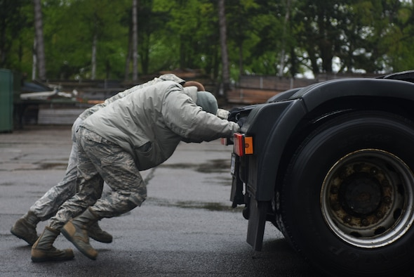 Airmen from the 48th Logistic Readiness Squadron push a tractor trailer during a ground transportation rodeo at Royal Air Force Lakenheath, England, April 27, 2018. The 48th LRS hosted a ground transportation rodeo where Airmen from the 100th and 48th LRS competed against each other in events to test their driving skills. (U.S. Air Force photo by Senior Airman Eli Chevalier)