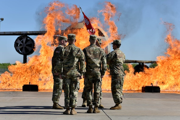 U.S. Army Lt. Col. Aaron Boher, 169th Engineer Battalion commander, passes the guideon to Capt. Brian Sekita, Delta Company 169th EN BN commander, on the fire pad at the Louis F. Garland Department of Defense Fire Academy on Goodfellow Air Force Base, Texas, April 27, 2018. The change of command ceremony is a time honored military tradition that signifies the orderly transfer of authority. (U.S. Air Force photo by Senior Airman Randall Moose/Released)