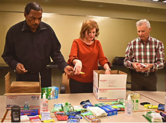 PETERSON AIR FORCE BASE, Colo. - James Foster (left), Holly Bernabei (center) and Mark Redpath pack care packages that will be sent to service members deployed to Kuwait. (Courtesy photo)