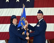 Col. Janette Thode, 340th Flying Training Group deputy commander, presents the 43rd Flying Training Squadron guidon to new squadron commander Lt. Col. Tom McElhinney during the April 27 change of command ceremony at Columbus Air Force Base, Mississippi. (U.S. Air Force photo courtesy of Columbus AFB)