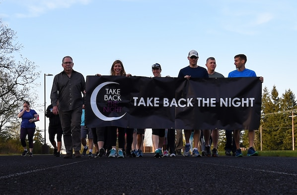 Team McChord leaders, sexual assault response coordinators and participants walk around a track during the Sexual Assault Prevention and Response Office's Take Back the Night 5K at Joint Base Lewis-McChord, Wash., April 25, 2018. The purpose of the event is to end sexual assault, raise awareness and support survivors of sexual assault. (U.S. Air Force photo by Senior Airman Tryphena Mayhugh)