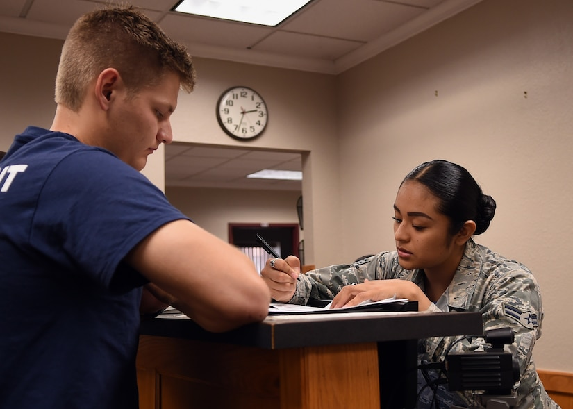Air Force Airman 1st Class Rosa Vittori, a personnel specialist with the Texas Air National Guard's 149th Fighter Wing, processes paperwork for Zach Pratka, a member of the wing's student flight at Joint Base San Antonio-Lackland, Texas, April 28, 2018. Texas Air National Guard photo by Airman 1st Class Katie Schultz