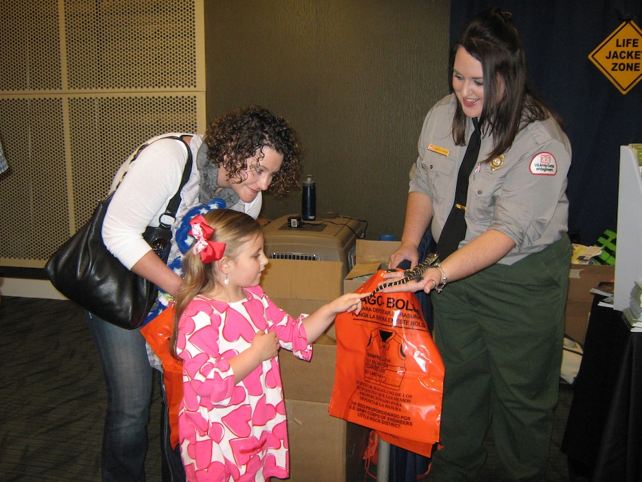 Natural Resource Specialist shows a young lady ACE the alligator at a water safety event.