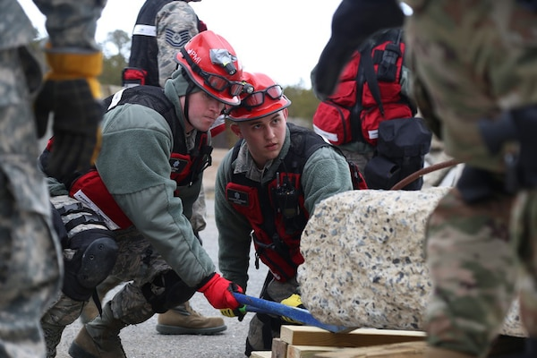Senior Airman Jesse D. Hyam and Staff Sgt. Alexander J. Barnhart, medical search and extraction team members assigned to the 157th Medical Group, N.H. Air National Guard, work to lift debris during a simulated exercise on April 11, 2018 at Joint Base Cape Cod, Mass. Hyam and Barnhart participated in a weeklong regional deployment readiness exercise as members of the N.H. CBRNE Enhanced Response Force Package team.