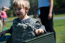A participant races while carrying empty ammunition cans during the 2018 Kid's Deployment Line, April 28, 2018, at Moody Air Force Base, Ga. The event allowed children the opportunity to experience what their parents go through while preparing to deploy. Children participated in obstacle courses, watched demonstrations and toured various aircraft and vehicles used by Airmen at Moody. (U.S. Air Force photo by Senior Airman Janiqua P. Robinson)