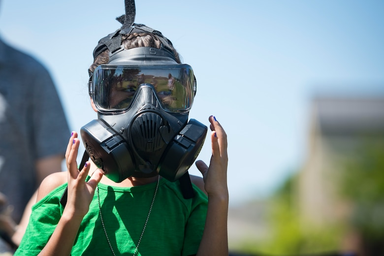 A participant tries on Mission Oriented Protective Posture or MOPP gear during the 2018 Kid's Deployment Line, April 28, 2018, at Moody Air Force Base, Ga. The event allowed children the opportunity to experience what their parents go through while preparing to deploy. Children participated in obstacle courses, watched demonstrations and toured various aircraft and vehicles used by Airmen at Moody. (U.S. Air Force photo by Senior Airman Janiqua P. Robinson)