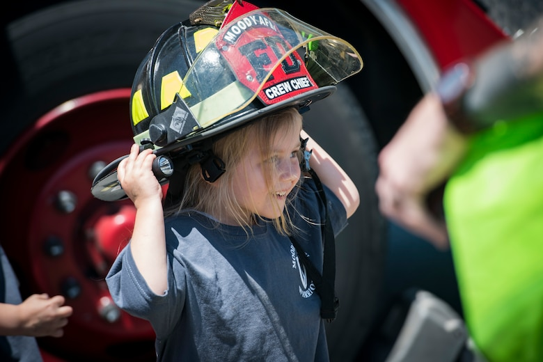 A participant tries on a firefighter helmet during the 2018 Kid's Deployment Line, April 28, 2018, at Moody Air Force Base, Ga. The event allowed children the opportunity to experience what their parents go through while preparing to deploy. Children participated in obstacle courses, watched demonstrations and toured various aircraft and vehicles used by Airmen at Moody. (U.S. Air Force photo by Senior Airman Janiqua P. Robinson)