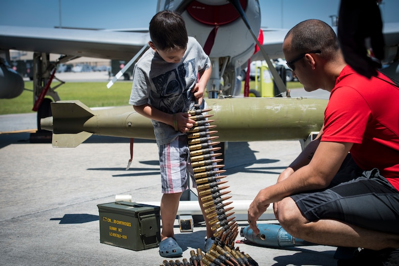 A participant handles .50 caliber rounds during the 2018 Kid's Deployment Line, April 28, 2018, at Moody Air Force Base, Ga.The event allowed children the opportunity to experience what their parents go through while preparing to deploy. Children participated in obstacle courses, watched demonstrations and toured various aircraft and vehicles used by Airmen at Moody. (U.S. Air Force photo by Senior Airman Janiqua P. Robinson)