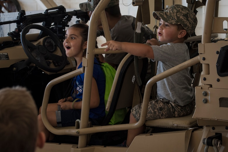 Participants sit in a military RZR all-terrain vehicle during the 2018 Kid's Deployment Line, April 28, 2018, at Moody Air Force Base, Ga. The event allowed children the opportunity to experience what their parents go through while preparing to deploy. Children participated in obstacle courses, watched demonstrations and toured various aircraft and vehicles used by Airmen at Moody. (U.S. Air Force photo by Senior Airman Janiqua P. Robinson)