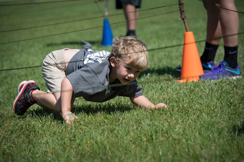 A participant crawls under a string obstacle during the 2018 Kid's Deployment Line, April 28, 2018, at Moody Air Force Base, Ga. The event allowed children the opportunity to experience what their parents go through while preparing to deploy. Children participated in obstacle courses, watched demonstrations and toured various aircraft and vehicles used by Airmen at Moody. (U.S. Air Force photo by Senior Airman Janiqua P. Robinson)
