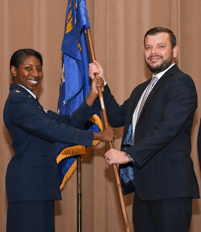 Maj. Jessica Sellers, commander of the 307th Force Support Squadron, presents the squadron flag to Brian Liesveld, the vice president of the Cyber Innovation Center, during an Honorary Commander's Induction Ceremony on Barksdale Air Force Base, La. April 29, 2018.