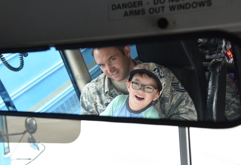 U.S. Air Force Tech. Sgt. Jason Repass, 81st Logistics Readiness Squadron vehicle operations control center supervisor, takes his son, Colton, on a bus tour during the 81st LRS Bring Your Child to Work Day event at the ground transportation yard at Keesler Air Force Base, Mississippi, April 26, 2018. The event allowed children the opportunity to experience what their parents do at work by touring facilities while receiving hands-on experiences. (U.S. Air Force photo by Kemberly Groue)