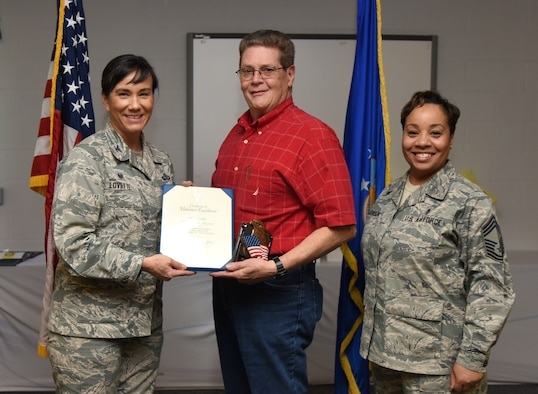 U.S. Air Force Col. Debra Lovette, 81st Training Wing commander, and Chief Master Sgt. Tanya Johnson, 81st Diagnostic and Therapeutics Squadron superintendent, presents Glen Picard, 81st Communications Squadron cyber support and security technician, with a Volunteer Excellence certificate during the 2018 Volunteer Appreciation Ceremony at the Sablich Center at Keesler Air Force Base, Mississippi, April 26, 2018. The event recognized Keesler personnel, family members and retirees for their volunteer service in 2017. (U.S. Air Force photo by Kemberly Groue)