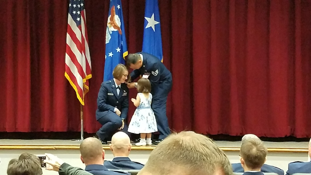 "Vesper M. Yasahardja kneels as her daughter Aubrey, 2, and husband, Staff Sgt. Matius ""Yoshi"" Yasahardja, pin the rank of second lieutenant onto her shoulders March 16 at Maxwell Air Force Base, Alabama."