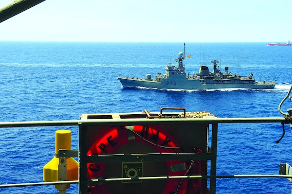 A Spanish patrol boat escorts the USG- owned MV Cape Ray through the Strait of Gilbraltar en route to the Mediterranean Sea. The USG modified and deployed the Cape Ray to dispose of Syrian chemical agents. (U.S. Navy/ Desmond Parks)