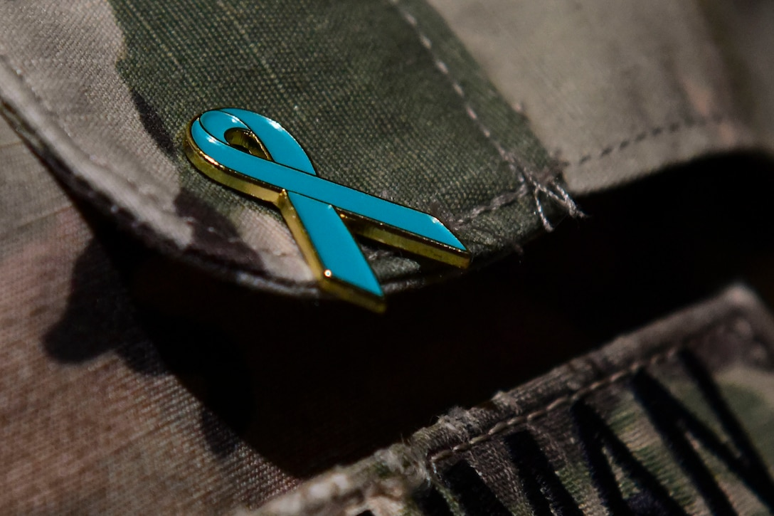 A teal ribbon pin adorns a pocket flap on a soldier's uniform.
