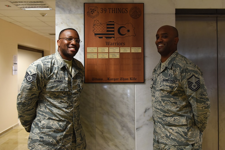 U.S. Air Force Master Sgt. Dexter Robinson poses with U.S. Air Force Staff Sgt. Christopher Atkins after Atkins' completion of the Titan University Warrior Program at Incirlik Air Base, Turkey, July 31, 2018.