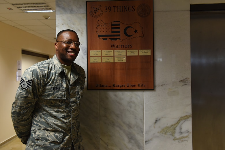 "U.S. Air Force Staff Sgt. Christopher Atkins, 39th Medical Operations Squadron medical technician, recieves a gold coin and a inscribed plaque on the ""Hall of Fame"" after completing the Titan University Warrior Program at Incirlik Air Base, Turkey, July 31, 2018."
