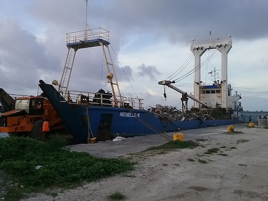 Truckers offload the scrap onto the first barge taking material away from Kwajalein Atoll.