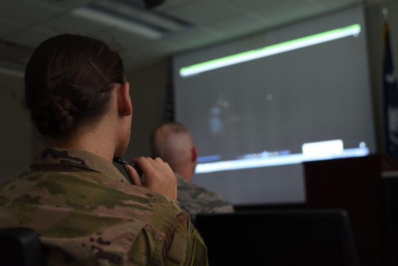 U.S. Airmen watch a video about the Air Force Office of Special Investigations (AFOSI) during an AFOSI recruiting team visit to the Spratt Education Center at Shaw Air Force Base, S.C., July 30, 2018.