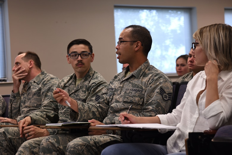 A U.S. Airman asks a question during a Headquarters Air Force Office of Special Investigations (AFOSI) recruiting team visit to the Spratt Education Center at Shaw Air Force Base, S.C., July 30, 2018.
