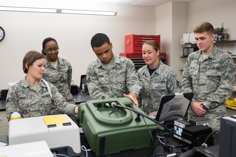 Tech. Sgt. Ashley Jordan, U.S. Air Force School of Aerospace Medicine Bioenvironmental Engineering Occupational Health Measurements Course director, second from right, instructs bioenvironmental engineering apprentice students on how to operate the HAPSITE ER portable gas chromatograph and mass spectrometer. The students are learning how to assemble the probe to the unit, install the gas canisters, install the battery, and prepare the system to identify and quantify trace amounts of an unknown substance that was captured from the air. (U.S. Air Force photo by Richard  Eldridge)