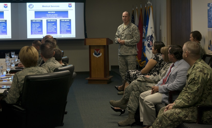 U.S. Air Force Lt. Col. Trevor Schar, 628th Medical Group deputy commander, presents slides during a mission brief for the Defense Health Agency and Air Force Surgeon General July 30, 2018, at Joint Base Charleston. The group visited JB Charleston to better understand the unique mission sets of the base and the needs of beneficiaries served by the 628th Medical Group.