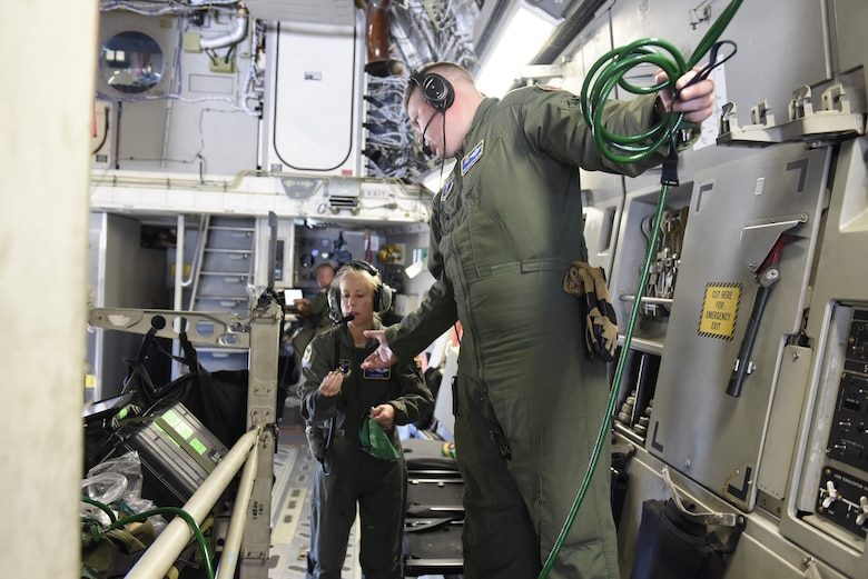 U.S. Air Force Lt. Col. Lisa Reeves (left) and Tech. Sgt. Joshua Albertin, members of the 156th Aeromedical Evacuation Squadron, attach important medical equipment to a North Carolina Air National Guard C-17 Globemaster III prior to taking off from North Carolina Air National Guard Base, Charlotte Douglas International Airport, for transport to Volk Field Air National Guard Base, Wisconsin, for a training exercise, July 9, 2018. (U.S. Air Force photo by Tech. Sgt. Nathan Clark)