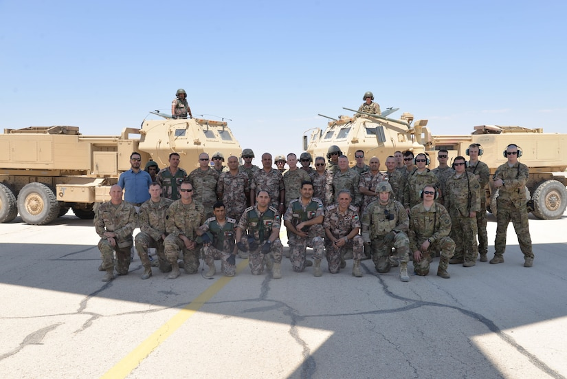 Soldier with Task Force Spartan and the Jordanian Army's 29th Royal HIMARS Battalion pose for a group photo after the launch of a Guided Multiple Launch Rocket from a Jordanian M142 High Mobility Artillery Rocket System (HIMARS) on July 23, 2018 during the Operation Lion Flight bi-lateral live-fire training exercise.