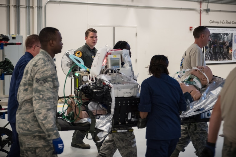 Staff Sgt. Travis Largent, Critical Care Air Transport Team initial course instructor, observes as students load critical patient-manikins in the back of a simulator fuselage. Largent and other instructors teach students how to package all the equipment needed for the patient to sustain treatment while being transported. (U.S. Air Force photo by Richard  Eldridge)