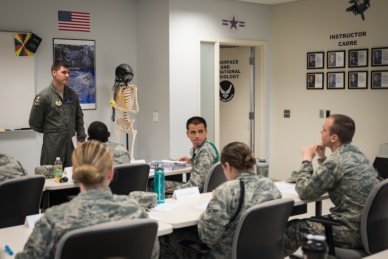 Staff Sgt. William Ensrud, aerospace physiology technician and assistant course director for aerospace and operational physiology apprentice course, listens to a student's question during the course. (U.S. Air Force photo by Richard  Eldridge)
