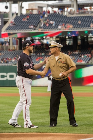 Major Gen. John R. Ewers Jr., staff judge advocate to the Commandant of the Marine Corps, shakes the hand of Washington Nationals catcher, Spencer Kieboom, during U.S. Marine Corps Day at Nationals Park, Washington D.C., July 31, 2018.