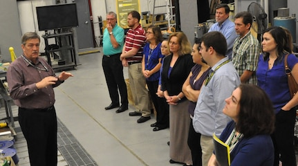 IMAGE: DAHLGREN, Va. (June 21, 2018) - Propel students review the Electromagnetic Railgun design parameters and test operations during a tour of the NSWC Dahlgren Division Electromagnetic Launch Facility conducted by Chester Petry, Chief Engineer for Electromagnetic Launch Weapons.  The Propel students discussed the use of electric weapons on future Navy combatants where the need for electric power will continue to grow and improve combat capability. Petry briefed the Warfare Centers' new supervisors during their tour of Dahlgren that included the Potomac River Test Range and the Human Performance Laboratory in addition to the Railgun Facility. The five-day Propel course provides an introductory level awareness of Warfare Center expectations and teaches a whole person supervisory approach that focuses on understanding supervisory responsibilities, practicing soft skills, and knowing where to go for situationally specific human resources support.  (U.S. Navy photo/Released)
