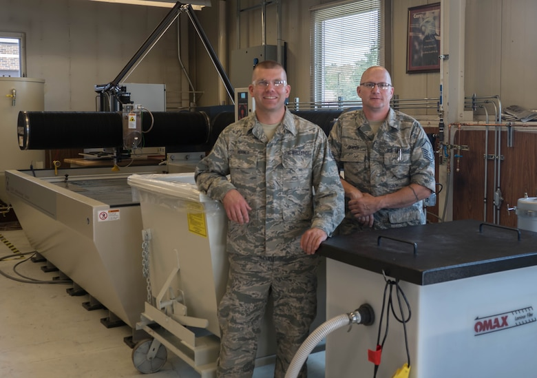 Tech. Sgt. Tyler Horner (left) and Master Sgt. Eric Johnson stand by the new Water Jet Machining Center at the 934th Maintenance Squadron Metal Fabrication shop. (Air Force Photo/Paul Zadach)