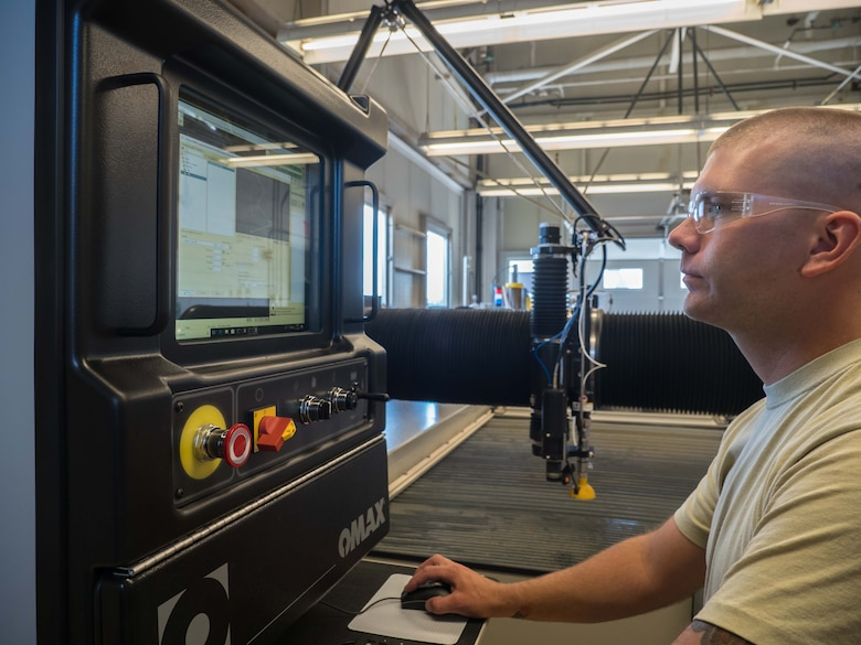 Tech. Sgt. Tyler Horner operates the water jet cutting machine. (Air Force Photo/Paul Zadach)