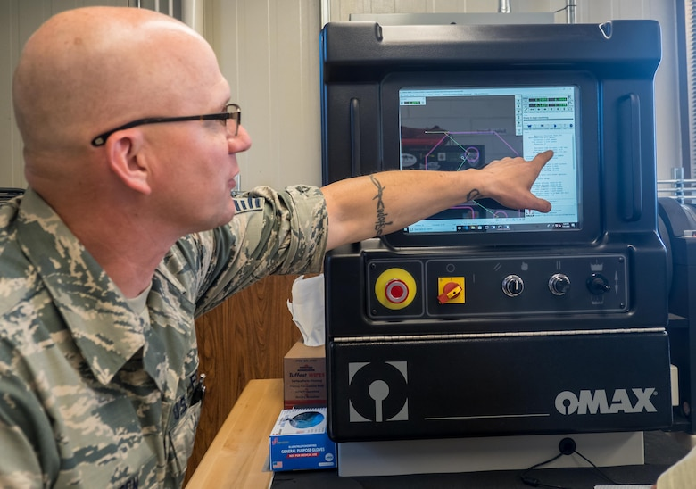 Master Sgt. Eric Johnson points out settings on the water jet machining center. (Air Force Photo/Paul Zadach)