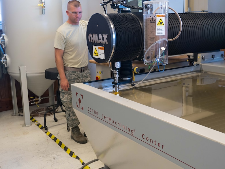 Tech. Sgt. Tyler Horner observes the water jet as a part is cut from aluminum stock. (Air Force Photo/Paul Zadach)