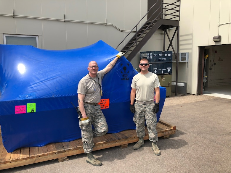 Master Sgt. Eric Johnson (left) and Tech. Sgt. Tyler Horner take delivery of the  OMAX Computer Numerical Control Waterjet Machining Center. (Air Force Photo/Paul Zadach)