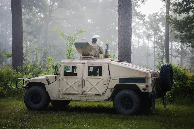 An Airman from the 822d Base Defense Squadron (BDS) scans the woods for simulated threats during a full mission profile assessment, July 24, 2018, at Moody Air Force Base, Ga. The 'Safeside' defenders evaluated their base defense tactics and procedures while performing patrols, tactical combat casualty care and countering improvised explosive devices for a mission readiness exercise. After successfully completing these events, the defenders are eligible to earn their Global Response Force status, which certifies the unit to deploy worldwide. (U.S. Air Force photo by Airman Taryn Butler)