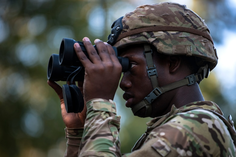 An Airman from the 822d Base Defense Squadron (BDS) scans the woods through his binoculars during a full mission profile assessment, July 24, 2018, at Moody Air Force Base, Ga. The 'Safeside' defenders evaluated their base defense tactics and procedures while performing patrols, tactical combat casualty care and countering improvised explosive devices for a mission readiness exercise. After successfully completing these events, the defenders are eligible to earn their Global Response Force status, which certifies the unit to deploy worldwide. (U.S. Air Force photo by Airman Taryn Butler)