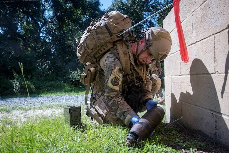 Tech. Sgt. Graham Speight, 822d Base Defense Squadron Explosive Ordnance Disposal team leader, inspects a simulated improvised explosive device, July 25, 2018, at Moody Air Force Base, Ga. The 'Safeside' defenders evaluated their base defense tactics and procedures while performing patrols, tactical combat casualty care and countering improvised explosive devices for a mission readiness exercise. After successfully completing these events, the defenders are eligible to earn their Global Response Force status, which certifies the unit to deploy worldwide. (U.S. Air Force photo by Airman 1st Class Eugene Oliver)