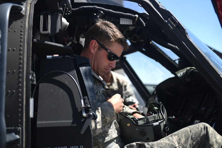 "U.S. Army CWC Tim Thrope, 96th Aviation Troop Command co-pilot assigned to JBLM, stows his aviation helmet at Fairchild Air Force Base, Washington, Aug. 1, 2018. Two Washington National Guard Blackhawks were staged at Fairchild to fight the wildfire dubbed ""The Sheep Creek Fire."" Washington National Guard efforts are currently focused on keeping the fire south of Sheep Creek, located north of Colville National Forest near the United States-Canadian border. Five 20-member local fire-fighting hand crews are already deployed fighting the fire, very soon to be aided by the WNG and its citizen soldiers. (U.S. Air Force photo/Airman 1st Class Whitney Laine)"