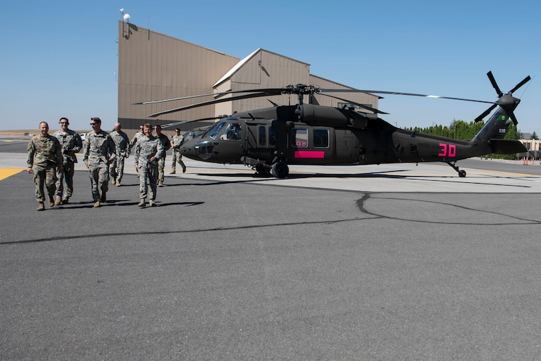 "U.S. Army aircrew members walk from two Washington National Guard Sikorsky UH-60 Blackhawks at Fairchild Air Force Base, Washington, Aug. 1, 2018. In the wake of Washington State Governor Jay Inslee declaring a wildfire state of emergency July 31, two Blackhawk helicopters launched from Joint Base Lewis-McChord, Washington, to Fairchild AFB to fight the wildfire dubbed ""The Sheep Creek Fire,"" which has consumed more than 20-acres of land so far. (U.S. Air National Guard photo/Tech. Sgt. Michael Brown)"