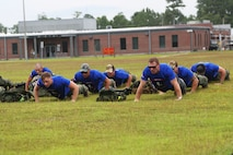 Marines and Sailors perform pushups at the Marine Raider Memorial March ceremony aboard Marine Corps Base Camp Lejeune, N.C., July 27, 2018. The ceremony marked the completion of the 900-mile march beginning in Mississippi and ending in North Carolina over the course of 10 days in honor of fallen Raiders. (U.S. Marine Corps photo by Sgt. Janessa K. Pon)