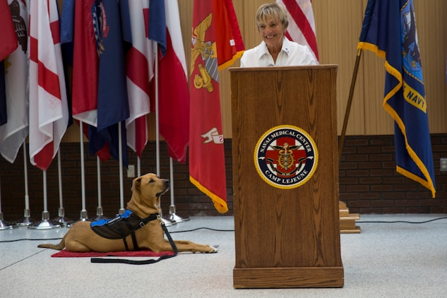 Sunnie Tortorici, a therapy dog trainer, explains the important role her trainee, Pappy Boyington, will play at the Naval Medical Center Camp Lejeune, N.C., July 10, 2018. According to the NMCCL, Pappy is part of the Canine Visitation Program which seeks to facilitate patient recovery, decrease stress levels, and provide a communication medium for patients, family and personnel. (U.S. Marine Corps photo by Lance Cpl. Nathan Reyes)