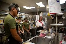 Evangeline Garcia, executive chef, Sodexo, demonstrates cake frosting to Marines at Mess Hall 128, Marine Corps Base Camp Lejeune, July 11. The training teaches Marine food service specialists methods to improve the basic services they provide involving baking, roasting, recipe use, cold food preparation and grilling. (U.S. Marine Corps photo by Lance Cpl. Ashley Gomez)